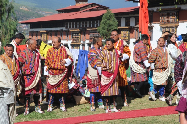 Men wear a gho at Paro Festival