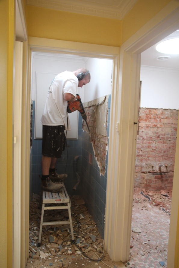 Cory jackhammers the toilet wall