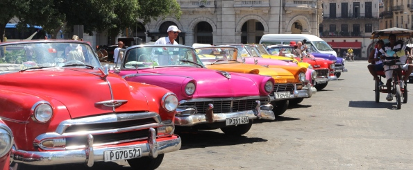 Vintage Cuban cars with bicycle taxi