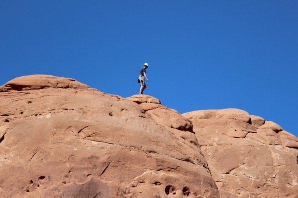 A climber on the rock beside the Balanced Rock