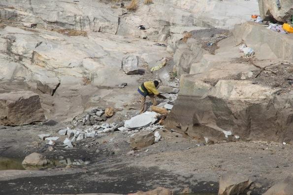Fellow knocking off large granite blocks